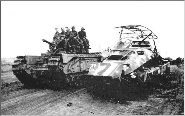 A Russian Churchil (lend lease) tank passes a destroyed 8 wheel armoured car of 19th Panzer Division.
