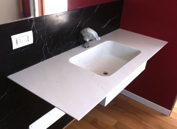 Bathroom vanity top in marble Giada White and wall tile in marble Nero Marquinia.