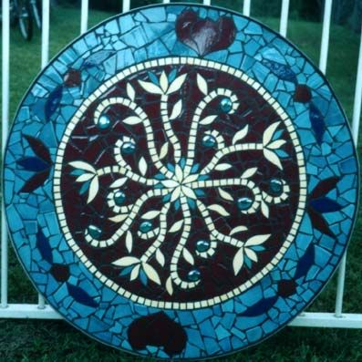 Stylised flowers featureing bright glass beads on an outdoor table base. Indian Flowers mosaic table in ceramic tiles by Brett Campbell Mosaics