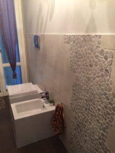 Rivestimento bagno in mosaico di sasso e gres porcellanato;