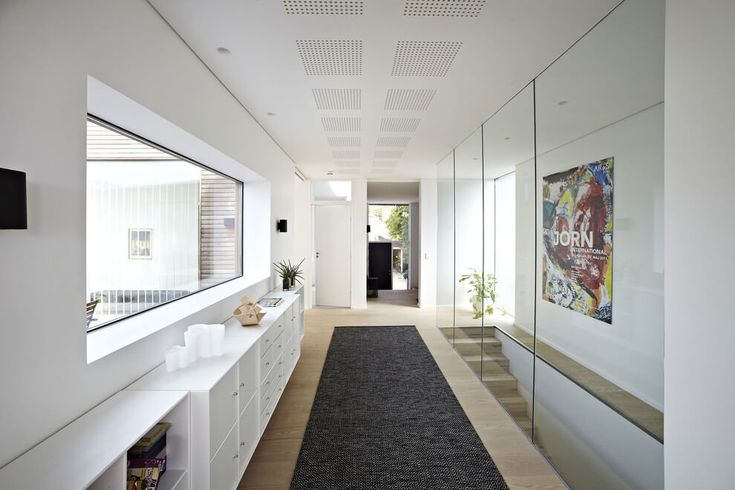 Cabinetry in a hallway of an open concept house adds storage.  House in Risskov by Per Dybro