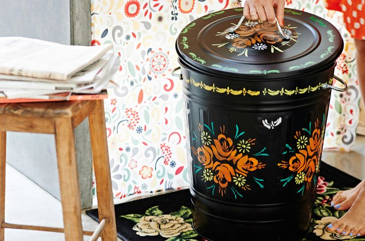 View of customized black KNODD bin on AKERKULLA rug with pattern wallpaper in background.