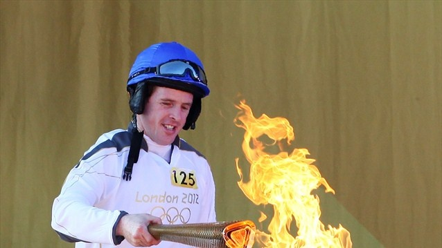 Horse racing jockey Jason Maguire lights the cauldron with the Olympic flame after arriving in Chester during Day 11 of the London 2012 Olympic Torch Relay.