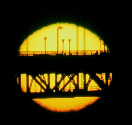 The upper rim is green while the lower one is red, as the sun sets behind the Golden Gate Bridge - Wikipedia