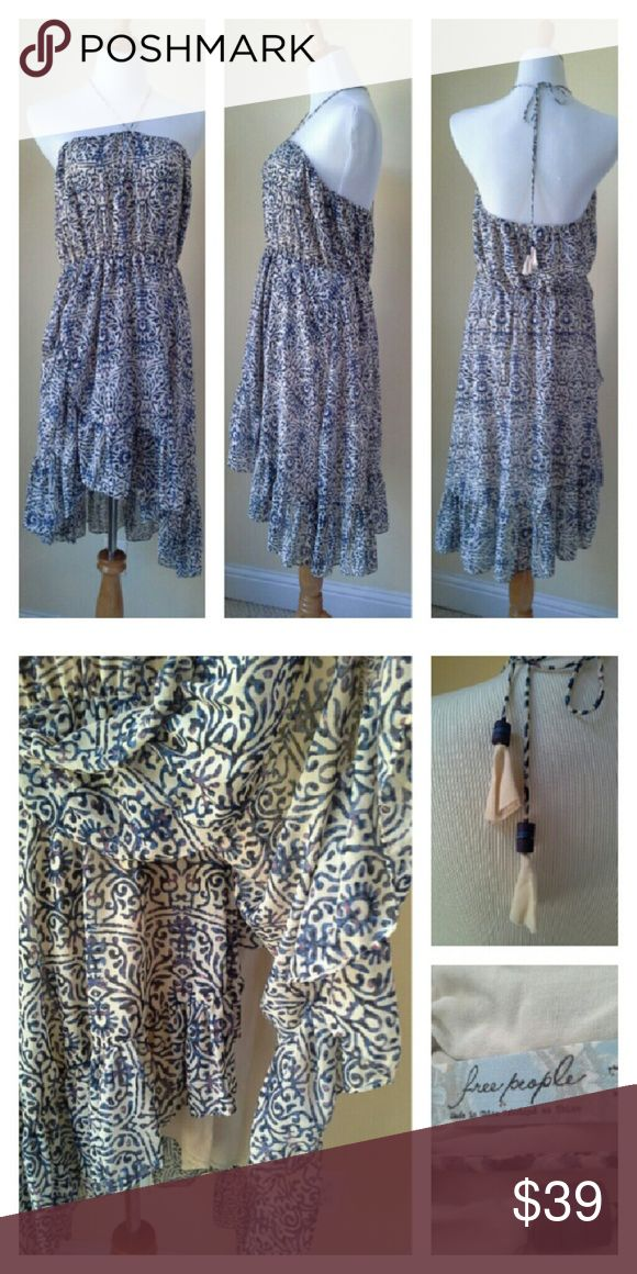 """FREE PEOPLE Indigo Sundress Billowy soft and flowy. Indigo blue with nude, and a tiny bit of purple. Spaghetti strap w beaded tassels that can be used for a halter neckline, or left to hang down the front if you're wearing as a strapless. Asymmetrical hem, with a ruffled edge, and off center faux wrap effect. A few unnoticeable snags well hidden in the pattern. Approx meas laid flat: elastic waist 15"""" across unstretched, open around top 17"""" acr unstretched, length front 28"""", back 32"""". Satin…"""