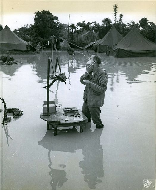 """Okinawa, 28 May 1945 by Marine Corps Archives & Special Collections, via Flickr. The caption on this photograph reads """"Indifferent-Completely ignoring that fact that his camp is half submerged by heavy Okinawa rains, Marine Staff Sergeant A.S. Barnacle, of Minneapolis, Minn., stands knee deep in water to shave at his """"Rube Goldberg"""" washstand."""""""