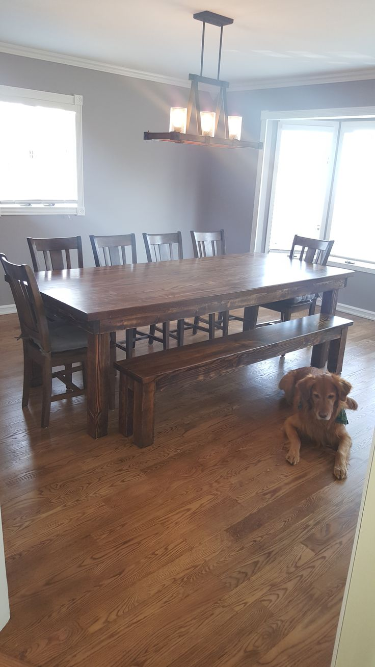 "James+James 8'x42"" Farmhouse Table with a custom Red Oak table top. This table has a traditional, boarded table top all stained in Vintage Dark Walnut. Pictured with matching Farmhouse Bench and 6 matching William Dining Chairs."