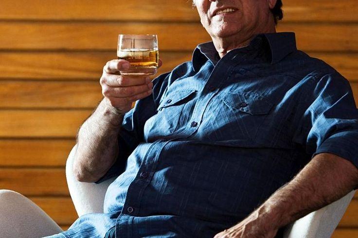 Senior man drinking scotch, smiling, portrait