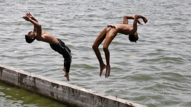 Two boys jump into the waters of the Sabarmati River to cool off themselves on a hot summer day in Ahmedabad, India as temperatures continue to eclipse 40 degrees Celcius.
