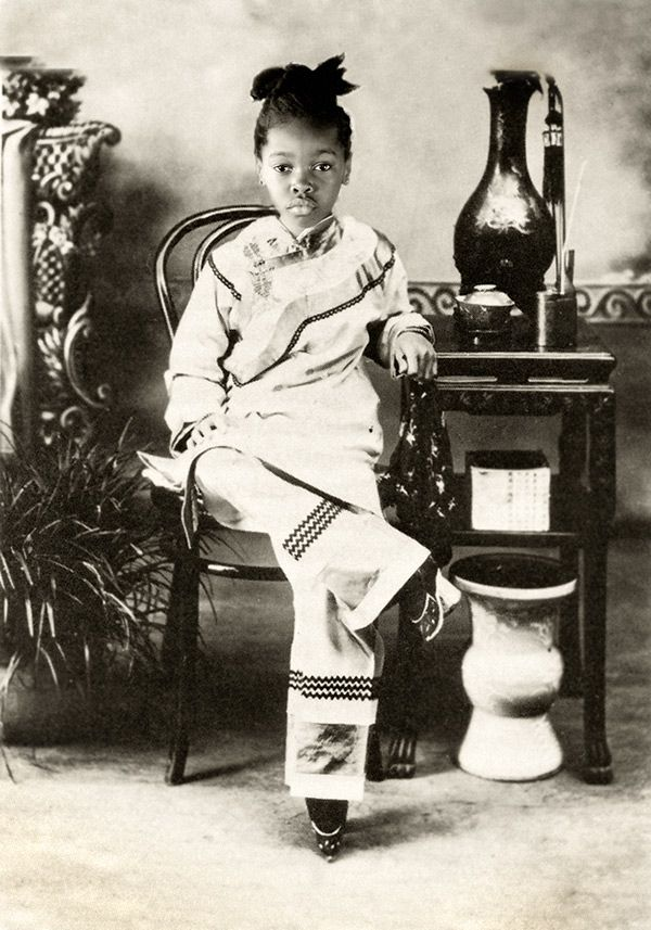 I find this fascinating since this girl appears to be of African decent based on bone structure, facial features and hair, but is in clothing with bound feet. Lotus Feet (Zakia as Chinese girl with bound feet) by Elena Kalis