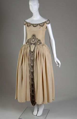 A gorgeous silk moiré Robe de Style from 1927 with an intricate beaded design. Made by Jeanne Lanvin, this gown was worn by Mrs. Charles S. Dewey when presented at the court of Saint James. This cut of dress was a popular alternative for the straight-cut frocks during the Flapper Era. The skirts were full while the bodice could either be straight or fitted. Sometimes the fullness of the skirt was even supported with eighteenth century-like paniers or hoops! This is only one of the couture…