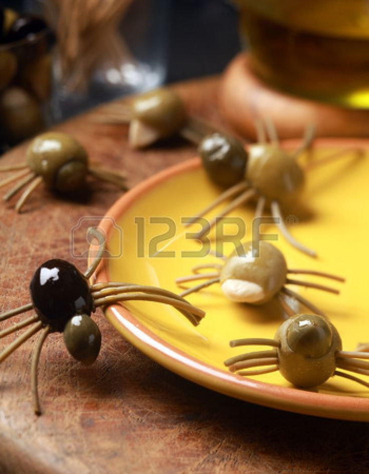 scary creepy halloween spider snacks served at a festive party made from cured green and black olives with pasta legs crawling all over the table from a