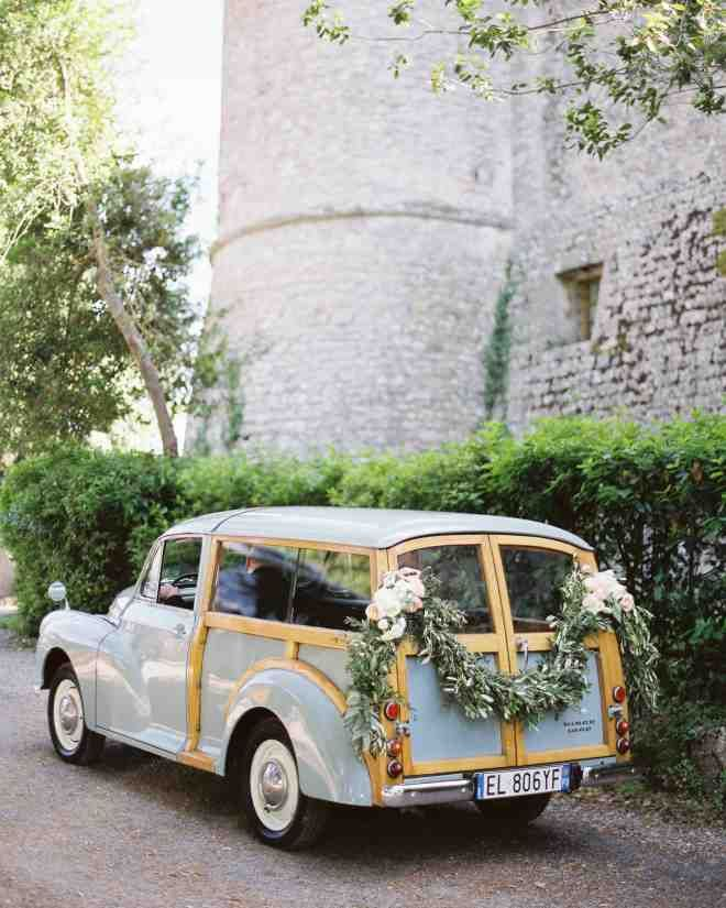 The groom's father escorted all three bridesmaids to the service in a vintage baby blue Morris Minor Traveller. The back of the car was adorned with a floral garland made up of roses, peonies, ranunculus, and other greenery.