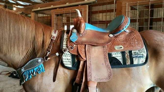 Used turquoise and tanned, tooled leather barrel western saddle for sale