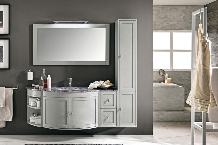 """Modular solution in silk grey finish.Base with doors, Lh open module and Rh module with drawer; domitilla wall-mounted tall unit with doors, single top in """"lilac viola"""" natural stone and undercounter ceramic washbasin, designo mirror.   #bathrooms 