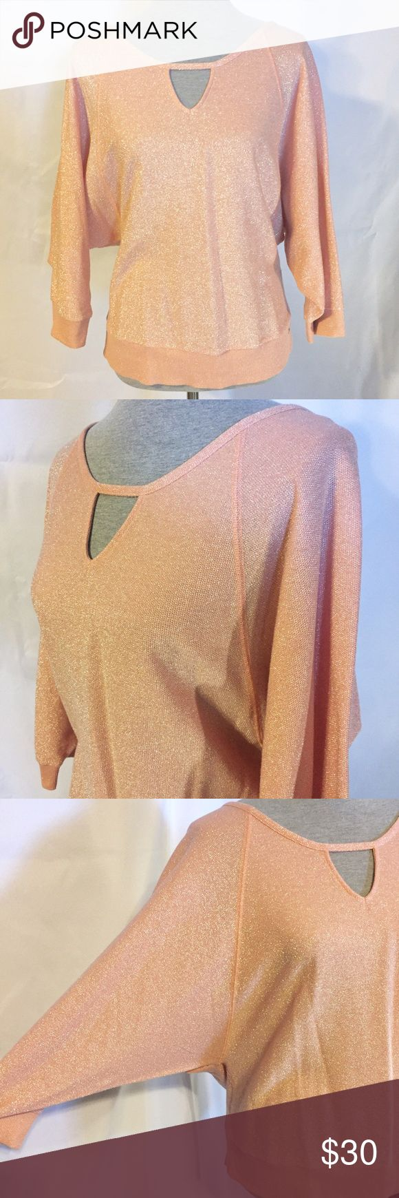 """Guess Coral Metallic Dolman Batwing Sleeve Large Absolutely gorgeous metallic batwing dolman sleeve top from Guess! The color borders on a pretty coral peach. Only worn maybe once or twice it is in Excellent condition! Very forgiving and flattering on any figure type. 50% Cotton, 34% Polyester, and 16% Metallic. Measures 25"""" long from shoulder to hem. Size Large from Guess Guess Tops"""