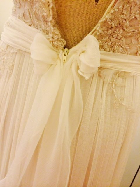 A soft, romantic bow, low-cut back and intricate lace and beading.