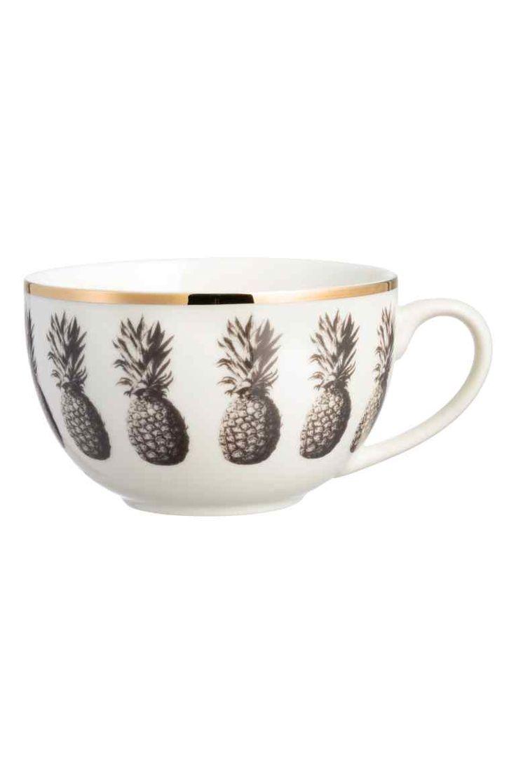 Tasse à motif d'ananas: Tasse en porcelaine imprimée d'un motif d'ananas avec  bord doré en haut. Hauteur 7,5 cm, diamètre en haut 11,5 cm.