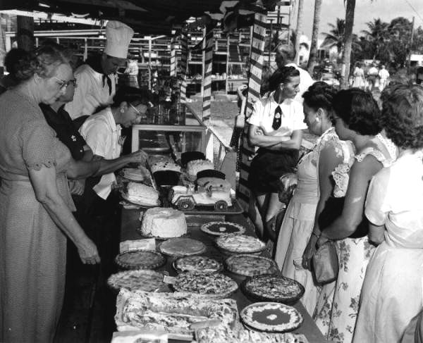 """Baking contest. Naples, Florida. 1950.Pies. Car shaped cake. Chef hat. """"The photograph was taken during Naples' Swamp Buggy Day baking contest."""" Department of Commerce collection. State Archives of Florida, Florida Memory"""
