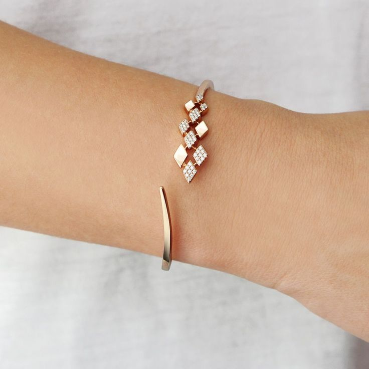 Staggered diamond and white gold diamond-shaped frames come together in perfect asymmetrical harmony with this luxe and contemporary cuff bracelet. The ideal statement piece, this cuff adds timeless, effortless glam to even the most casual looks.