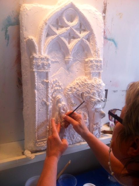 Plaster bas-relief panel sculpted by Ellie Ellis. She is using this panel as an example to teach students.