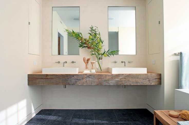 Perfectly modern bathroom features a reclaimed wood floating dual washstand mounted between ivory walls and fitted with rectangular vessel sinks positioned beneath satin nickel faucets mounted on the wall beneath inset medicine cabinets.