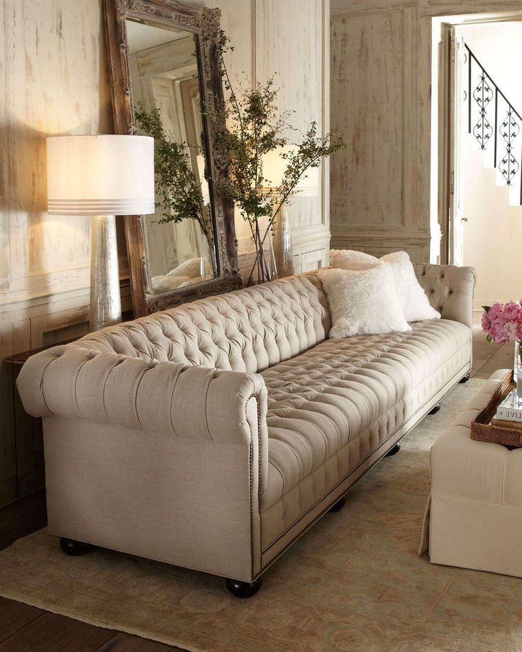 Made in the United States. Elegant and striking oversized chesterfield sofa in beautiful cream beige linen fabric. This couch is handcrafted and features button tufting, cotton/polyester linen upholstery, espresso brown ball legs, rolled arms and nailhead trim. Perfect in french country, traditional, contemporary, transitional, modern and hollywood regency inspired decor. This piece will surely make a statement in your living room.