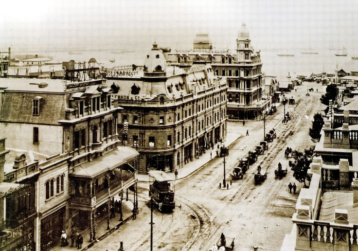 Adderley Street, Cape Town c1900 | An undated view of lower Adderley Street showing, at left, a tram making its way between the Grand Hotel and the premises of Lennon & Co. At the water's edge at right a sign advertises a skating rink while beyond that, in Table Bay, a number of ships lie at anchor. In the centre of the road a number of horse-drawn carriages are parked while other horse-drawn transports make their way into the city.