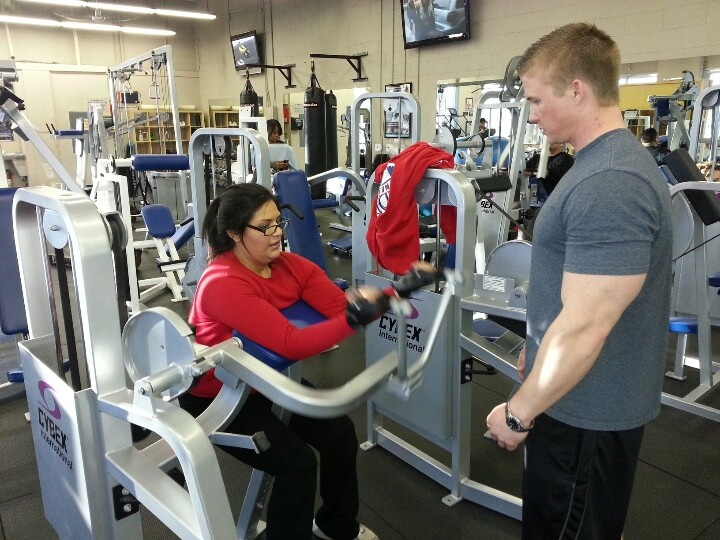 Patty squeezing out preacher curls with BBF Trainer, Jason Alexander.