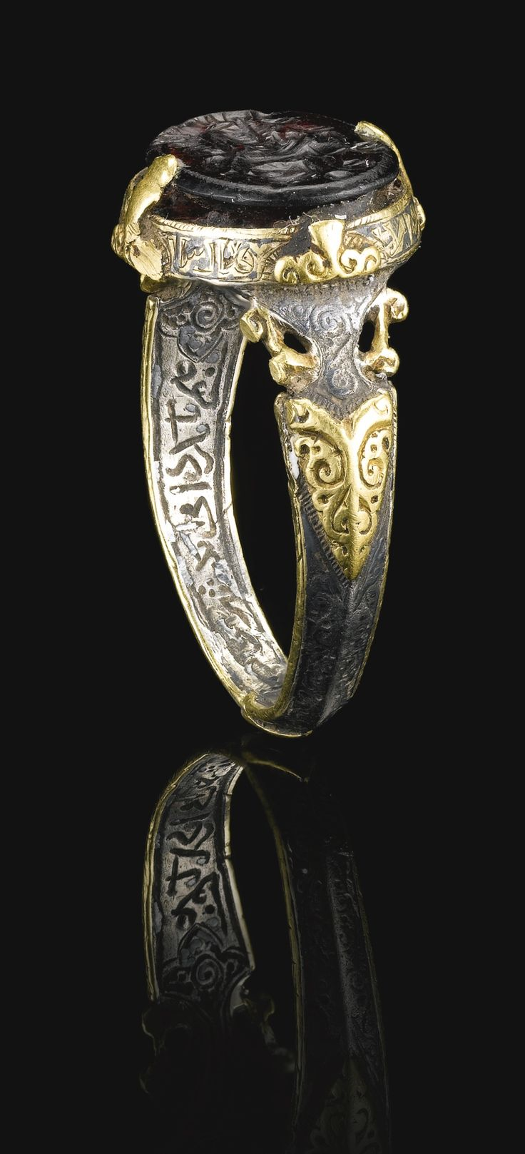 A fine and rare Seljuk silver and gold ring set with a deep purple stone seal bearing the name of Ali Ibn Yusuf, Persia, 12th century