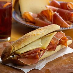Jamón Serrano and Manchego Cheese Sandwich - Bocadillo de Jamón: http://www.tienda.com/recipes/bocadillo.html  Whenever we arrive in Barajas airport in Madrid, we immediately head over to one of the many cafes and order a café con leche, then a delicious bocadillo de jamón with thin slices of serrano ham and Manchego cheese on a fresh baguette. Add some extra virgin olive oil and piquillo peppers for a sandwich that is quintessentially Spanish - fresh, simple and delicious!