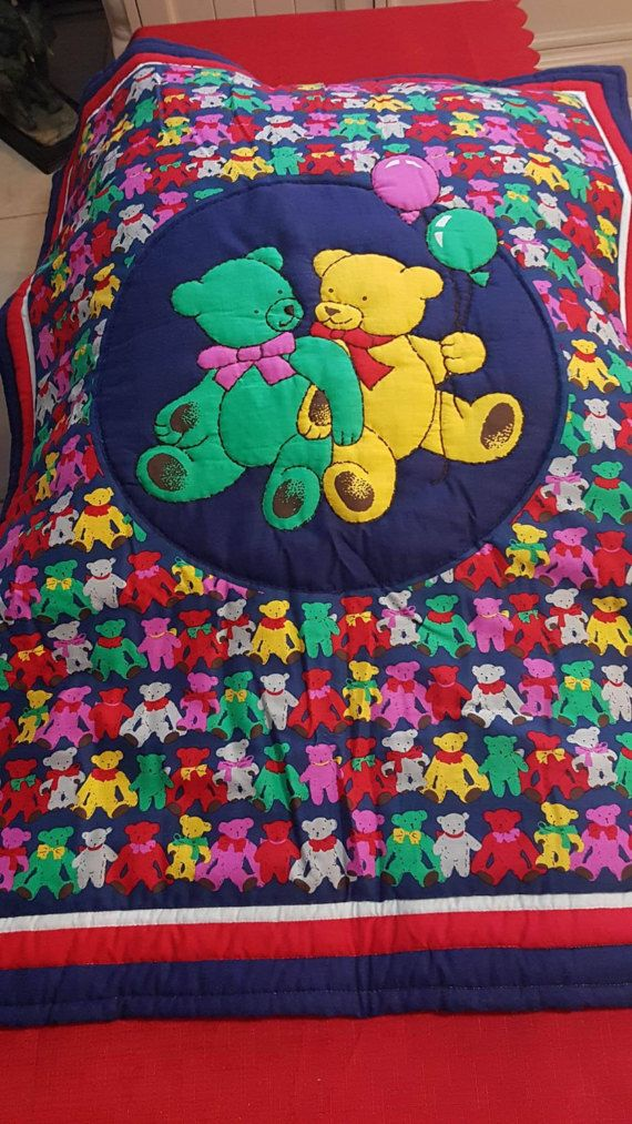 Unisexed Bright Teddy Bears , on a navy background. Navy and Red border, with a red back  Machine Quilted. Quilt Cotton Panel with polyester wadding. Perfect for little ones with allergies. Quilt measures 74 cm wide by 93 cm long  Perfect for cot or toddler bed. Could also be used as a floor mat. Completely washable in machine in cold water and hang dry. No bleach or bleach like products Ready to be posted. At Mean Mothers Creations we can create a one of a kind quilt just for you, please…