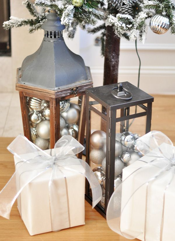Fill outdoor lanterns with ornaments as an alternative to the standard hurricane vase! Would look fabulous on a dining table too.