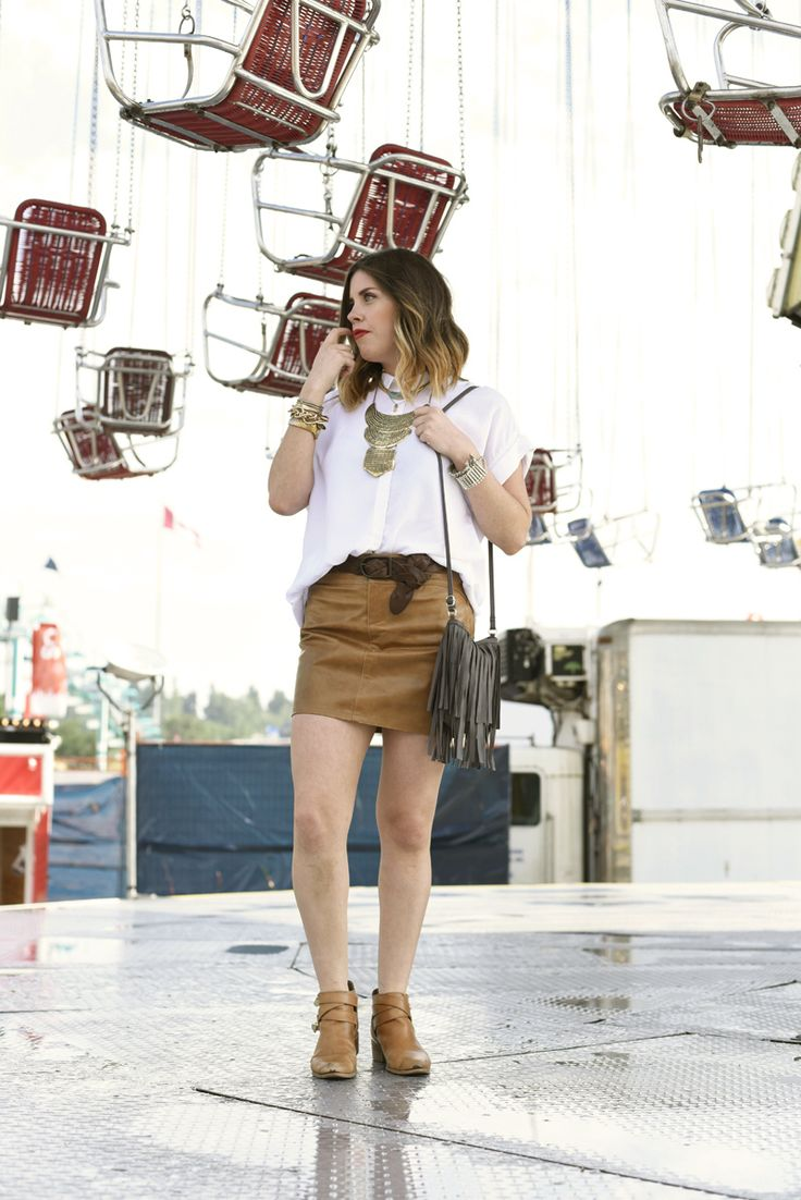 Jill wearing her Calgary Stampede outfit - white oversized button down tunic, leather skirt, leather belt, fringe tassel leather purse and worn in booties