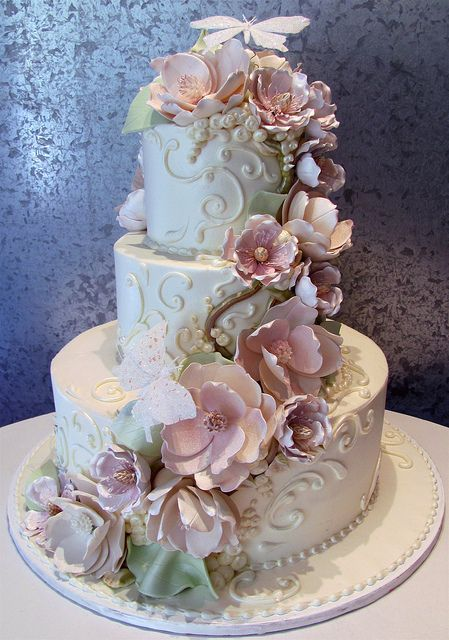 Butterfly Cascade Wedding Cake - Tiered filigree design with gumpaste flowers and butterflies.