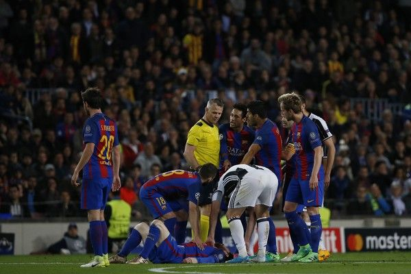 Barcelona players gather around Barcelona's Argentinian forward Lionel Messi (DOWN) after a clash during the UEFA Champions League quarter-final second leg football match FC Barcelona vs Juventus at the Camp Nou stadium in Barcelona on April 19, 2017. / AFP PHOTO / Marco BERTORELLO