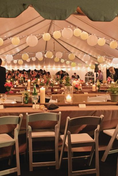 Lanterns and cafe lights add a warm glow to the tent at this backyard wedding. Ask Canton Chair Rental how to get this look!