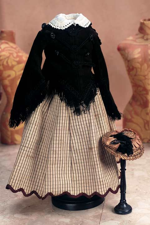 Black cashmere fitted jacket with V-shaped draping over the hips, very wide pagoda-style sleeves, braid and silk fringe trim, over a blouse with beautifully-embroidered cutwork collar; tan silk taffeta skirt with interwoven lines of dark brown and black has a scalloped hem edged with brown silk; woven bronze-green bonnet trimmed with brown and black silk and feathers. Circa 1865.