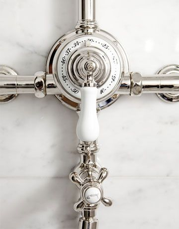 Polished Carrara marble tiles, Candide tub, étoile tub filler, faucets, and showerhead, Normandy sinks, and vanity mirrors from Waterworks: waterworks.com.