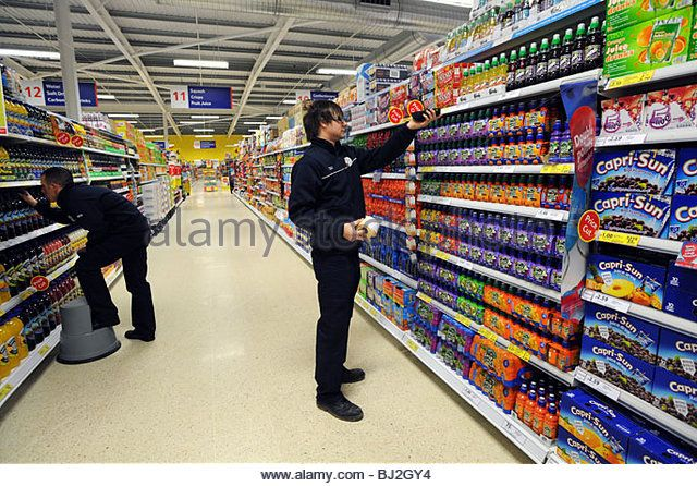 Workers stock the shelves and check prices in a Tesco store - Stock Image