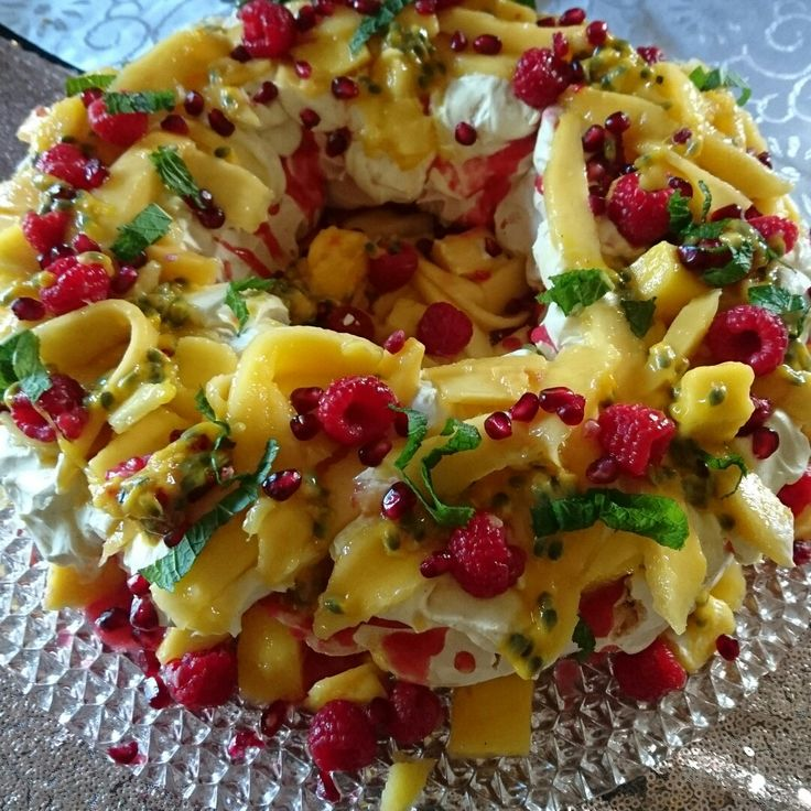 My amazing mango and raspberry pavlova.  Home made pavlova covered with lashings of raspberry coulis dollops of vanilla bean whipped cream, cubes and slices of fresh mango, fresh raspberries, passionfruit, pomegranate seeds and mint leaves. YUMMMAAAYY