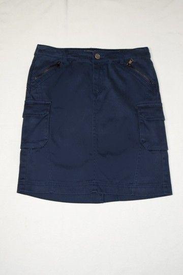 Falda tejana Laura Jo de color azul marino. Cierre de botón y cremallera. Dos bolsillos delanteros con cierre de cremallera y dos laterales con cierre de botón a presión. Abertura en el bajo.