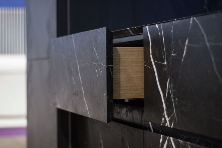 Piqu kitchen with full stone fronted drawers in black marble.