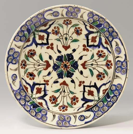 AN IZNIK POTTERY DISH Ottoman Turkey, circa 1600 With sloping rim on short foot, the white interior painted in red, blue and green with black outlines, decorated with a central rosette surrounded by four arabesques interlaced with stems and alternating with floral sprays springing from small stylised vases, the rim with blue and white stylised wave and scroll border, the exterior with stylised blue and green motifs, 12 1/8in. (30.5cm.) diam.
