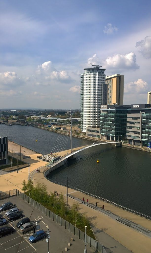 "From the top of the The Imperial War Museum North, on Trafford Wharf Road, Salford Quays, Manchester, England, designed by architect Daniel Libeskind (1946), with a view on the Media City Foodbridge over the Manchester Ship Canal, designed by Wilkinson Eyre Architects and engineered by Balfour Beatty, and on the BBC Offices and ""The Heart"" Apartment Tower, also designed by Wilkinson Eyre Architects."