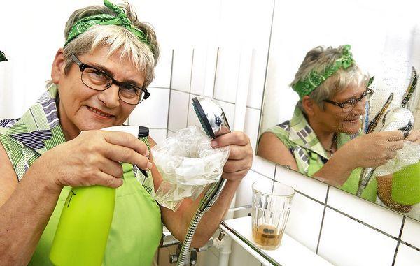 Fru Grøn rengører brusehoved med eddike
