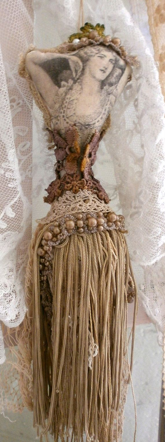 This is an art doll to collect. Made in tassel form.  Sculpted and stuffed body  16 inches tall.  Embellished with beads, hand dyed lace and fringe. Frays