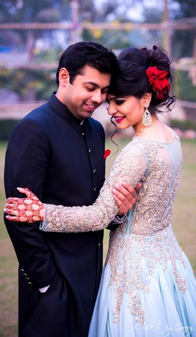 Candid Copule Shot - Bride in a Light Blue Sheer Gown | WedMeGood | Light Blue Sheer Gown with Diamond Jewelry and Rose in Hair, Groom in a Black Band Gala Sherwani #wedmegood #indianbride #sherwani #blue #sheer #gown #diamonds #indiangroom #candidcouple #candid #indianwedding