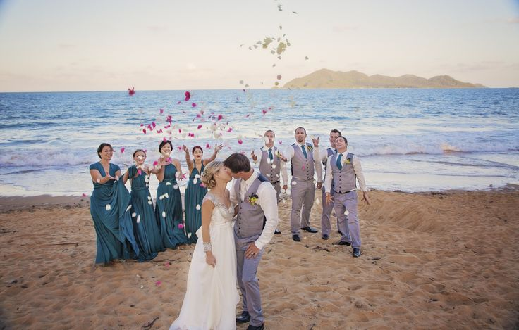A gorgeous group shot with the famous Dunk Island in the background. Petals thrown by the bridesmaids and groomsmen make for a timeless picture!