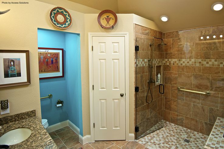 A southwestern bathroom with checkered tile and a glass shower door creates a comfortable and relaxing space. Cultural artwork also adds character to the neutral walls.
